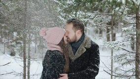 Unga härliga caucasian par som tillsammans kysser under trendiga millennials för en insnöad vinterskog som har gyckel arkivfilmer