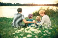 Unga härliga föräldrar som kramar deras unga söner på solnedgången nära sjön Familj som promenerar floden Fotografering för Bildbyråer