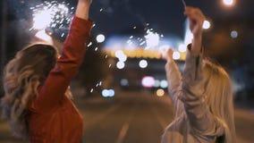 Unga härliga flickor med tomtebloss som lyckligt upp till dansar med deras musik för händer i nattstaden långsam rörelse lager videofilmer