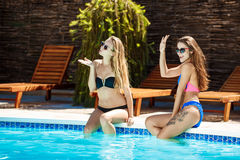 Unga härliga flickor som ler och att hälsa, avslappnande near simbassäng Royaltyfria Bilder