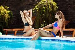 Unga härliga flickor som ler och att solbada, avslappnande near simbassäng Royaltyfri Bild