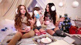 Unga härliga gladlynta flickor säger, skrattar, ler, vilar på partiet för ` s för det nya året, drinkte för tre systrar och äter  lager videofilmer