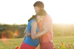 Unga härliga gravida par i vallmofält Royaltyfria Bilder
