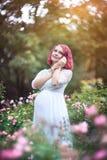 Unga härliga kvinnaist som står i trädgården av rosa rosor w Arkivbild