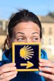 Unga härliga kvinnliga pilgrims stående som poserar med den typiska Camino de Santiago blåtttegelplattan Arkivbilder