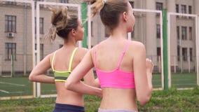 unga härliga kvinnor för stående två Dem som är inkörda sommarstadion En i hörlurar lyssnar till musik tillbaka sikt lager videofilmer