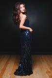 Unga härliga lockiga kvinnor blänker in klänningen på mörk bakgrund Mode Begreppsberöm royaltyfria bilder