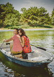 Unga härliga lyckliga älska par som ror ett litet fartyg på en sjö Ett roligt datum i natur Par i ett fartyg Arkivbild