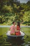 Unga härliga lyckliga älska par som ror ett litet fartyg på en sjö Ett roligt datum i natur Par som kramar i ett fartyg Arkivfoto