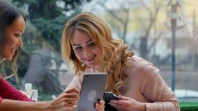 Unga härliga lyckliga kvinnor som använder minnestavlan i kafé Arkivbilder
