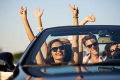 Unga härliga mörker-haired unga kvinnor med vänner i solglasögon ler och rider i en svart cabriolet på vägen arkivbilder