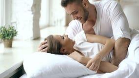 Unga härliga och älska par vaknar upp på morgonen Den attraktiva mankyssen och kramar hans fru i säng arkivfilmer