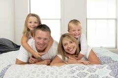 Unga härliga och strålningsgammal le lycklig posera sötsak för par som 30 till 40 år ligger på säng med den lilla sonen och härli Arkivfoto