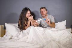 Unga härliga och stressade par i säng som ser graviditetstestkänsla som är lycklig och som är förvånad vid positivt gravid se för arkivbilder