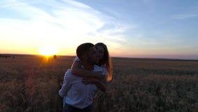 Unga härliga par i ett vetefält Kontur på solnedgångbakgrund långsam rörelse stock video