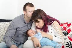 Unga härliga par med nytt behandla som ett barn hemma Royaltyfri Bild