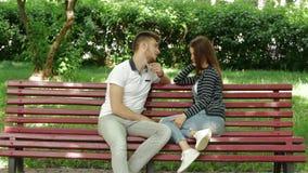 Unga härliga par på en bänk i Park samtalet arkivfilmer