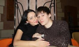 Unga härliga par sitter i kafé på tabellen, kram Arkivbilder