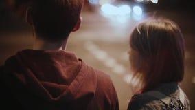 Unga härliga par som går i stadsmitten i afton Lycklig man och kvinna som korsar vägen, i trafiktid stock video