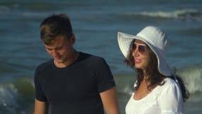 Unga härliga par som går vid havet Pojke och flicka De är lyckliga Solen skiner ljust Blå himmel långsam rörelse close upp stock video