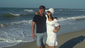 Unga härliga par som går vid havet Pojke och flicka De är lyckliga Solen skiner ljust Blå himmel långsam rörelse dem arkivfilmer