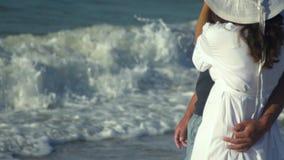 Unga härliga par som går vid havet Pojke och flicka De är lyckliga Solen skiner ljust Blå himmel långsam rörelse dem lager videofilmer