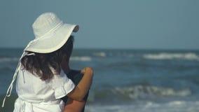 Unga härliga par som går vid havet Pojke och flicka De är lyckliga Solen skiner ljust Blå himmel långsam rörelse Grabben stock video