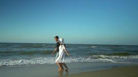 Unga härliga par som går vid havet Pojke och flicka De är lyckliga Solen skiner ljust Blå himmel långsam rörelse De kör stock video