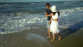 Unga härliga par som går vid havet Pojke och flicka De är lyckliga Solen skiner ljust Blå himmel långsam rörelse Vågorna arkivfilmer