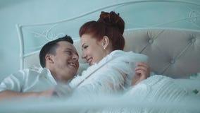 Unga härliga par som har gyckel i säng, henne som klämmer honom på kinden stock video