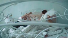 Unga härliga par som har gyckel i säng, slåss de av kuddar som passerar kameran längs sängen, ultrarapid lager videofilmer