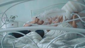 Unga härliga par som har gyckel i säng, slåss de av kuddar som skrattar, ultrarapid arkivfilmer