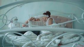 Unga härliga par som har gyckel i säng, slåss de vid kuddar och att skratta som passerar kameran längs säng, ultrarapid arkivfilmer