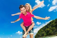 Unga härliga par som har gyckel på en tropisk strand Arkivfoton