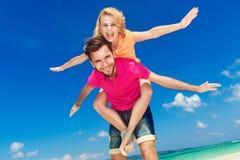 Unga härliga par som har gyckel på en tropisk strand Fotografering för Bildbyråer