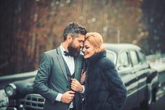 Unga härliga par som kopplar av tillsammans att gå på en retro bil arkivfoto