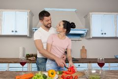 Unga härliga par som kramar i köket som tillsammans lagar mat en sallad De ler p? de arkivbild