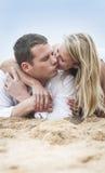 Unga härliga par som kysser på strandsand Royaltyfri Foto