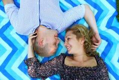 Unga härliga par som ler och ligger på filten på gräset i parkera Royaltyfri Foto