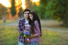 Unga härliga par som omfamnar och ler på solnedgången i sommar royaltyfri fotografi