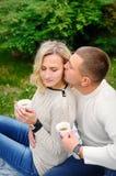 Unga härliga par som omfamnar under en filt i parkera Arkivfoto