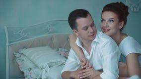 Unga härliga par som sitter i morgonen på sängen som ut ser fönstret stock video
