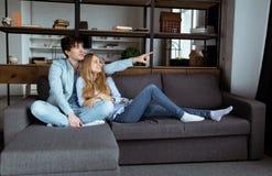 Unga härliga par som tillsammans sitter på den hållande ögonen på TV:N för soffa royaltyfri foto