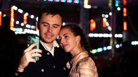 Unga härliga par som tillsammans spenderar tid på datumet som tar selfieståenden med smartphonen i nöjesfält på natten arkivfilmer