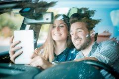 Unga härliga parvänner som använder minnestavlan Arkivbilder