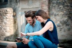 Unga härliga parvänner som använder minnestavlan Arkivfoto