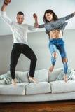 Unga härliga roliga par man den förälskade kvinnan ha rolig banhoppning från säng inomhus hemma Royaltyfria Bilder