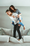 Unga härliga roliga par man den förälskade kvinnan ha rolig banhoppning från säng inomhus hemma royaltyfri fotografi