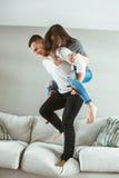 Unga härliga roliga par man den förälskade kvinnan ha rolig banhoppning från säng inomhus hemma royaltyfri bild