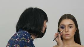 Unga härliga sexiga flickamodeller gör blå afton att utgöra rökiga ögon och med falska ögonfrans Ögon med mång--färgat lager videofilmer